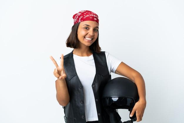 Junge frau, die einen motorradhelm lokalisiert auf weißem lächeln hält und siegeszeichen zeigt