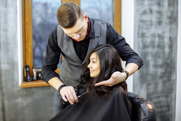 Junge frau, die einen neuen haarschnitt am frisörsalon erhält.
