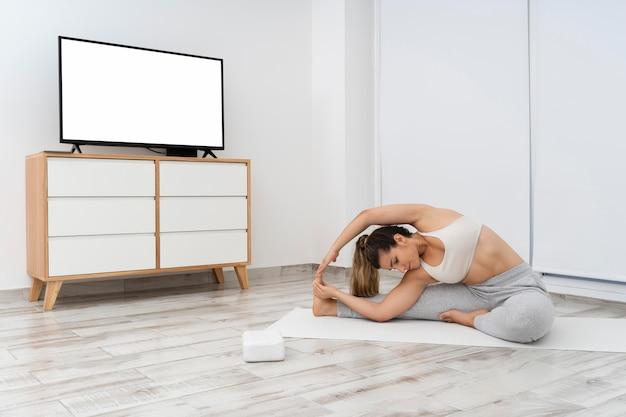 Junge frau, die einen online-yoga-kurs auf ihrem fernseher macht