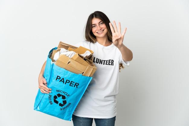 Junge frau, die einen recyclingbeutel voll papier hält, um auf weiß glücklich zu recyceln und vier mit den fingern zu zählen