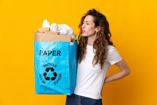 Junge frau, die einen recyclingbeutel voll papier hält, um zu recyceln