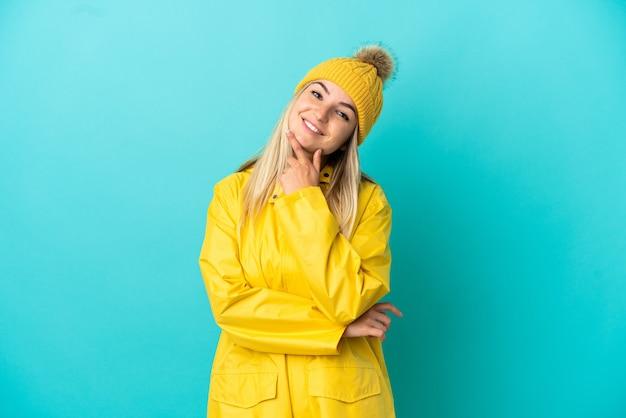 Junge frau, die einen regendichten mantel über isoliertem blauem hintergrund trägt, glücklich und lächelnd
