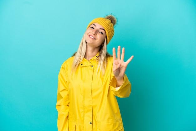 Junge frau, die einen regendichten mantel über isoliertem blauem hintergrund trägt, glücklich und zählt vier mit den fingern