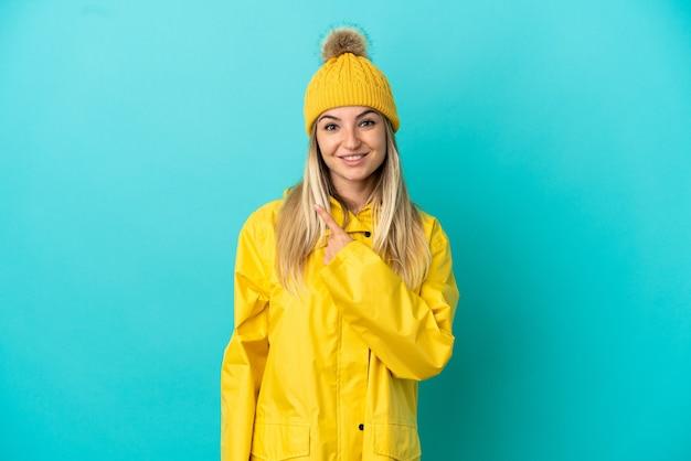 Junge frau, die einen regendichten mantel über isoliertem blauem hintergrund trägt und auf die seite zeigt, um ein produkt zu präsentieren