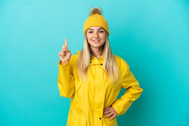 Junge frau, die einen regendichten mantel über isoliertem blauem hintergrund trägt und auf eine großartige idee hinweist