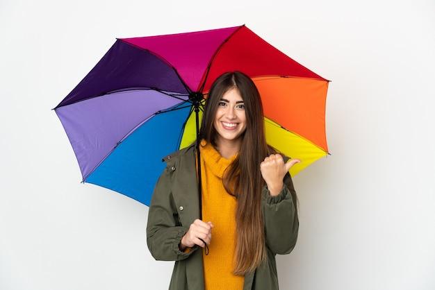 Junge frau, die einen regenschirm lokalisiert auf weißer wand hält, die zur seite zeigt, um ein produkt zu präsentieren