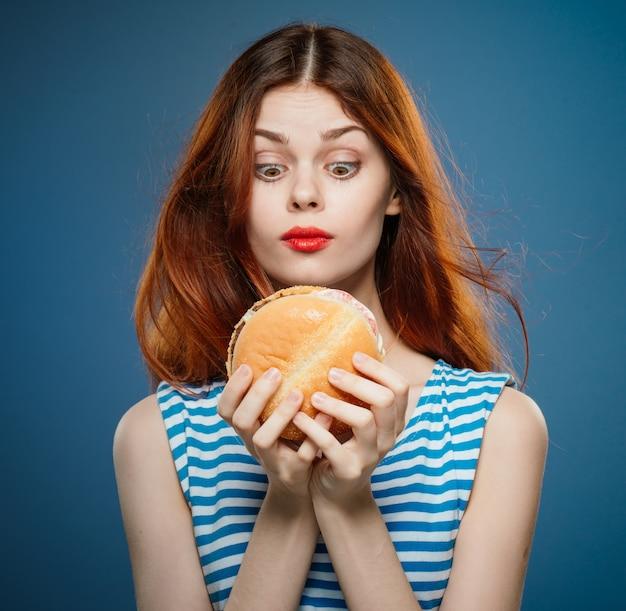 Junge frau, die einen saftigen burger, köstlichen fast-food-hamburger isst