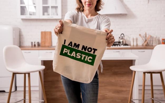 Junge frau, die einen stoffbeutel hält. in der küche. ich bin kein plastik. kampagne zur reduzierung des einsatzes von plastiktüten. kein verlust