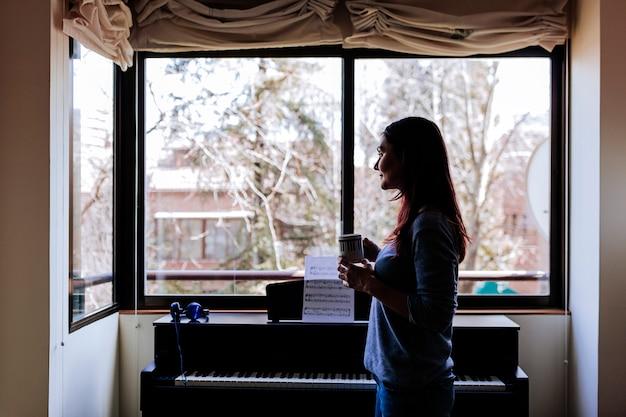 Junge frau, die einen tasse kaffee hält und bereit ist, klavier zu spielen, indem sie ein musikblatt liest.