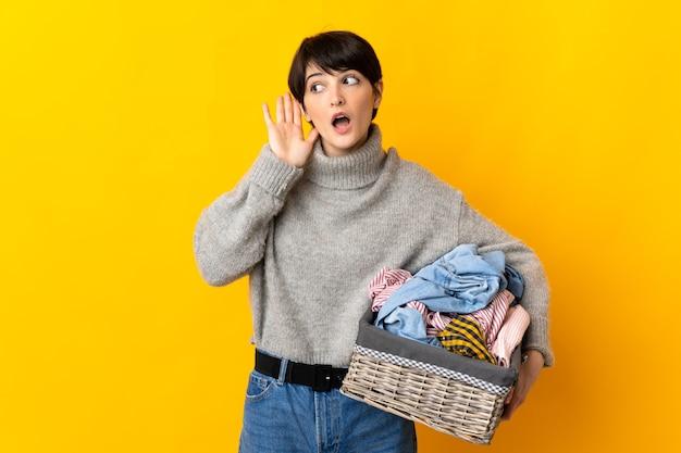 Junge frau, die einen wäschekorb hält, der etwas hört, indem man hand auf das ohr legt