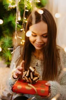 Junge frau, die einen weihnachtsbaum hält