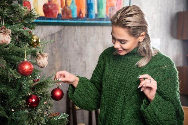 Junge frau, die einen weihnachtsbaum verziert, hängt eine rote kugel auf