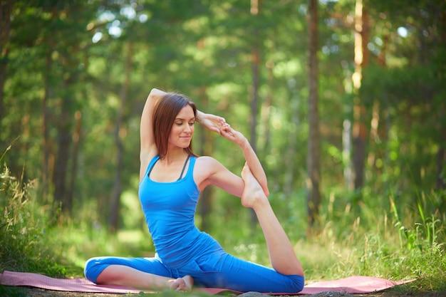Junge frau, die einige gymnastische bewegungen zu üben