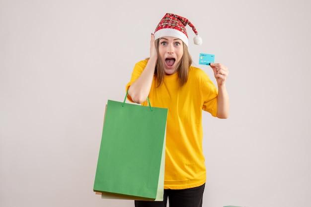 Junge frau, die einkaufspakete und bankkarte auf weiß hält