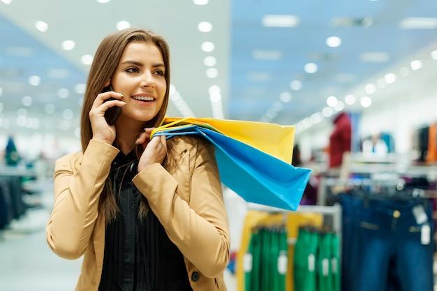 Junge frau, die einkaufstaschen hält und per telefon spricht