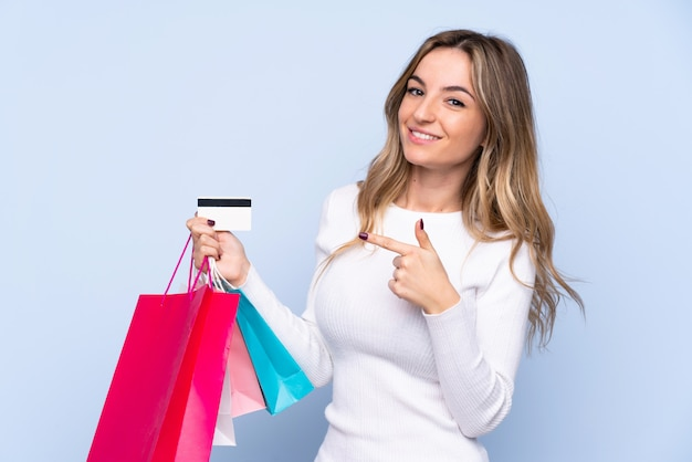 Junge frau, die einkaufstaschen und eine kreditkarte hält
