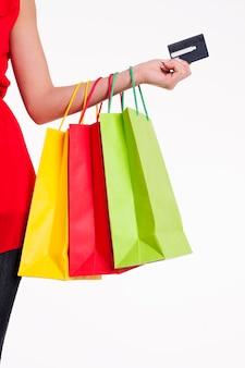 Junge frau, die einkaufstaschen und kreditkarte hält