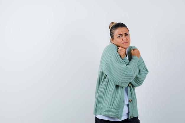 Junge frau, die einschränkung oder x-geste in weißem t-shirt und mintgrüner strickjacke zeigt und gehetzt aussieht