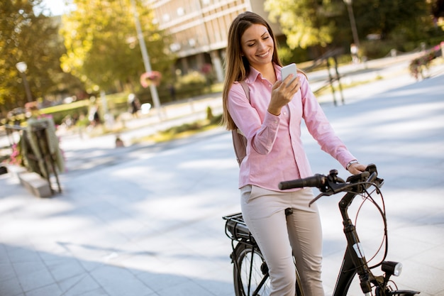 Junge frau, die elektrisches fahrrad fährt und handy in der städtischen umwelt verwendet