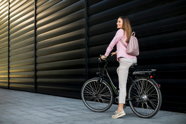 Junge frau, die elektrisches fahrrad in der städtischen umwelt fährt