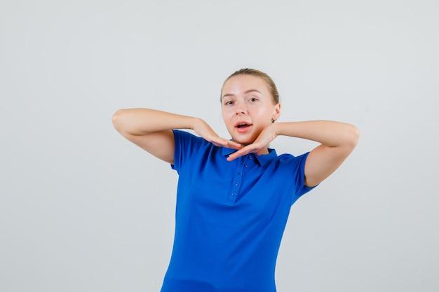 Junge frau, die ellbogen im blauen t-shirt streckt und freudig schaut