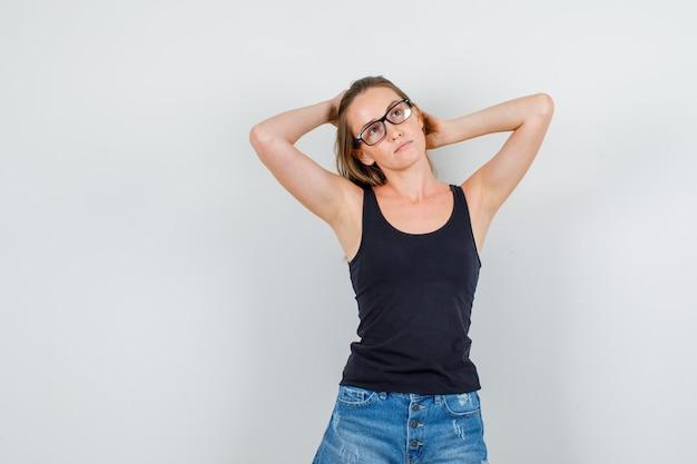 Junge frau, die erhobene hände auf haar in unterhemd, shorts, brille hält und nachdenklich schaut