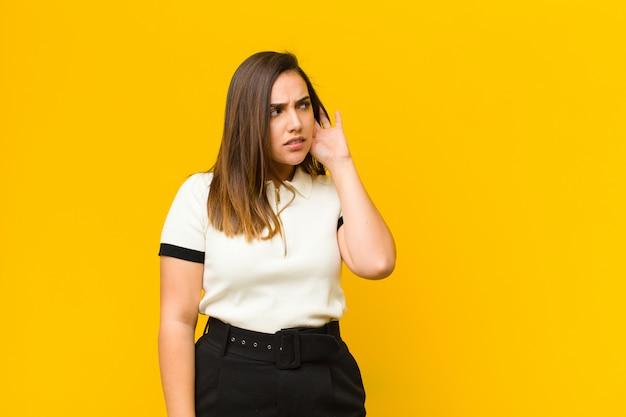 Junge frau, die ernst und neugierig aussieht, zuhört, versucht, ein geheimes gespräch oder klatsch zu hören, isoliert auf orange wand lauscht