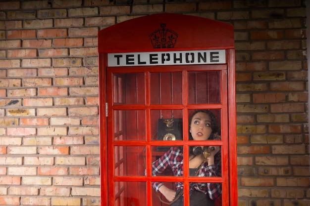 Junge frau, die ernsthaft in einer geschlossenen roten telefonzelle mit einem backsteinmauer-hintergrund spricht.