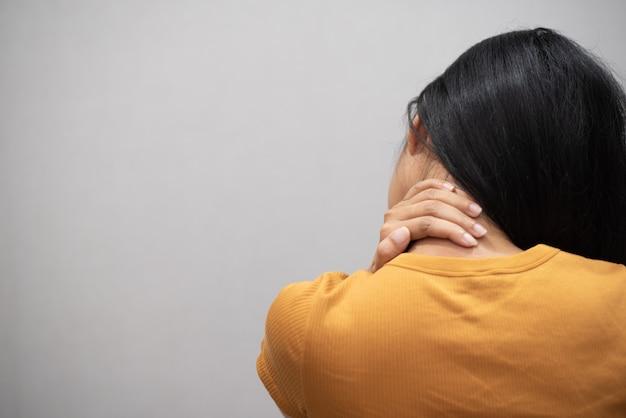 Junge frau, die erschöpft sich fühlt und unter nackenschmerzen leidet