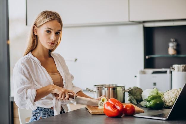 Junge frau, die essen an der küche zubereitet
