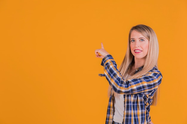 Junge frau, die etwas auf einem orange hintergrund zeigt