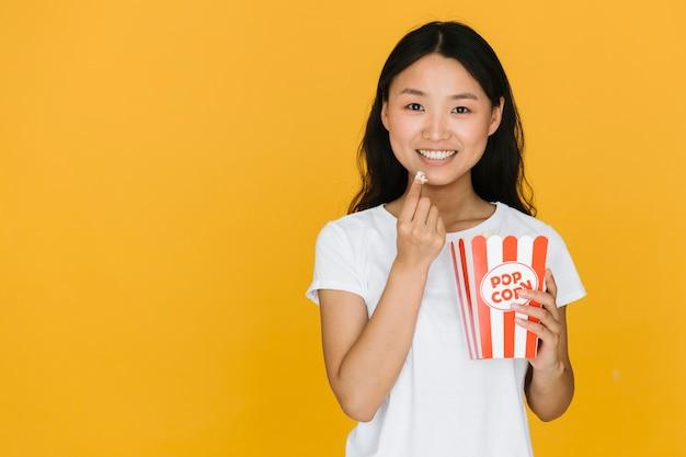 Junge frau, die etwas popcorn mit kopienraum isst