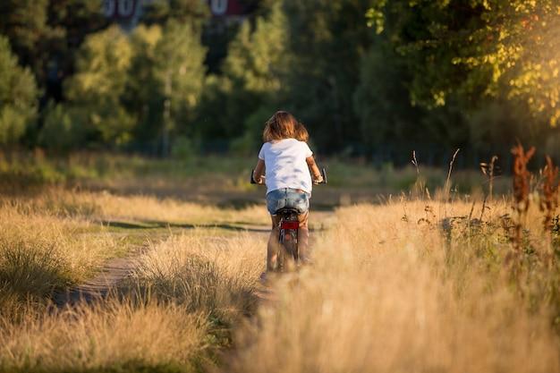 Junge frau, die fahrrad auf wiese auf feldweg fährt
