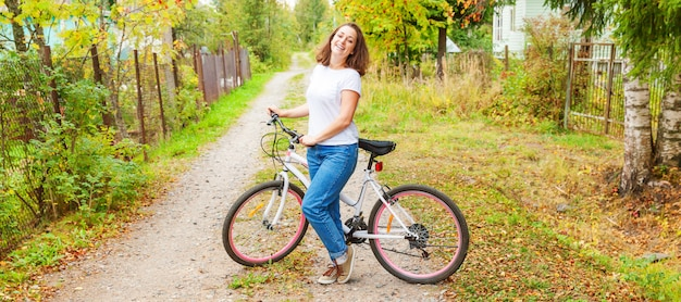 Junge frau, die fahrrad im sommerstadtpark im freien reitet. aktive menschen. hipster mädchen entspannen und fahrer fahrrad. radfahren zur arbeit am sommertag. fahrrad- und ökologie-lebensstilkonzept.