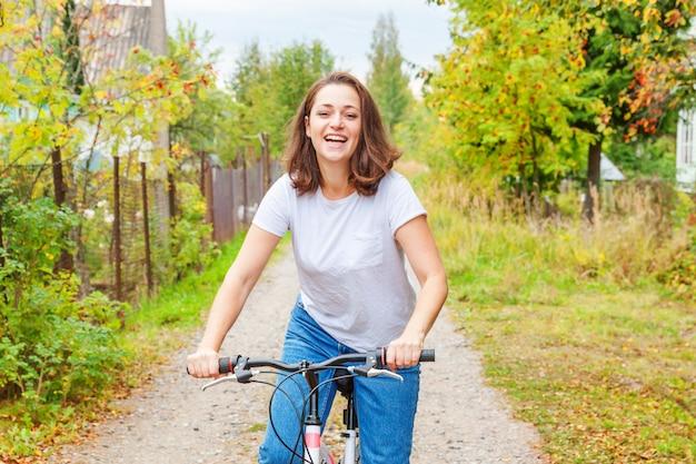 Junge frau, die fahrrad im sommerstadtpark im freien reitet