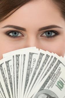 Junge frau, die fan des porträts der hundert dollarnoten hält. augen nahaufnahme schuss