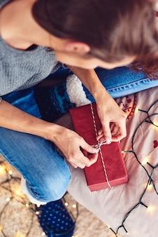 Junge frau, die feiertagsgeschenk verpackt