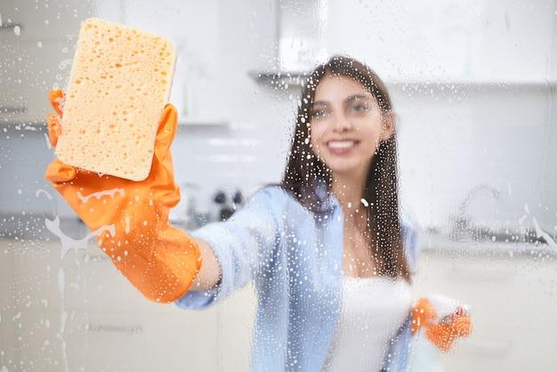 Junge frau, die fenster mit lappen und waschmittel wäscht