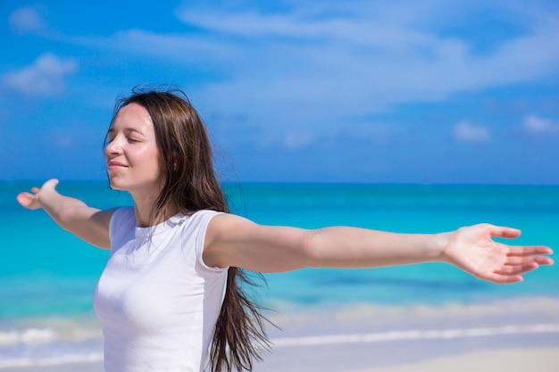 Junge frau, die ferien auf weißem tropischem strand genießt