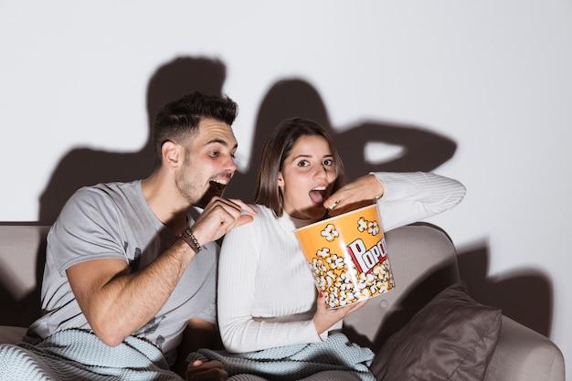Junge frau, die fernsieht und popcorn nahe mann auf sofa isst