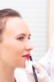 Junge frau, die festes make-up auf ihren lippen im kosmetikersalon hat. permanent makeup (tätowierung). zeichnen einer kontur mit einem weißen lippenstift. vertikales foto Premium Fotos
