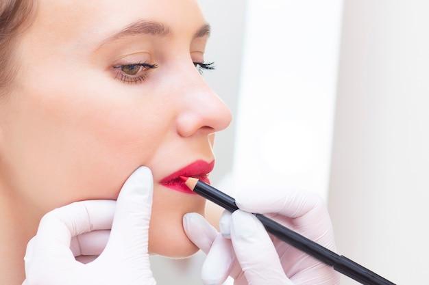 Junge frau, die festes make-up auf ihren lippen im kosmetikersalon hat. permanent makeup zeichnen einer kontur mit einem weißen lippenstift