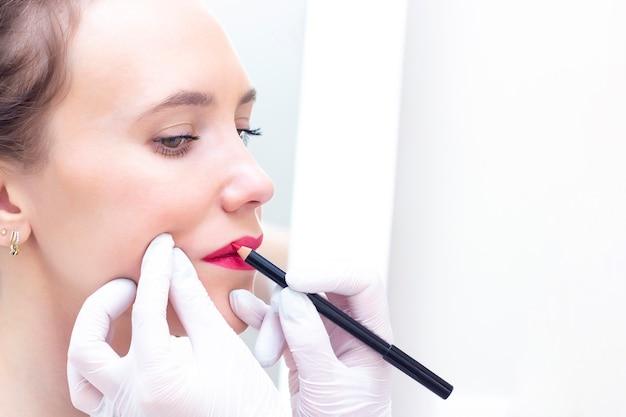 Junge frau, die festes make-up auf ihren lippen im kosmetikersalon hat.
