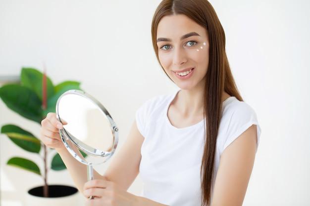 Junge frau, die feuchtigkeitscreme auf ihrem gesicht vor dem spiegel anwendet