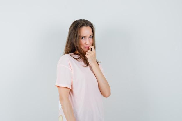 Junge frau, die finger auf ihrer lippe im rosa t-shirt hält und beschämt aussieht. vorderansicht.