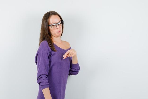 Junge frau, die finger unten im violetten hemd zeigt und angewidert aussieht. vorderansicht.