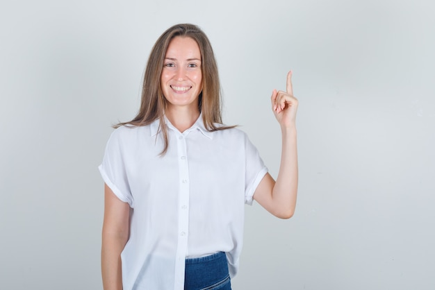 Junge frau, die finger zeigt und im weißen t-shirt lächelt