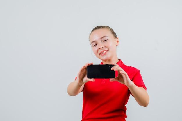 Junge frau, die foto auf handy in rotem t-shirt nimmt und fröhlich schaut