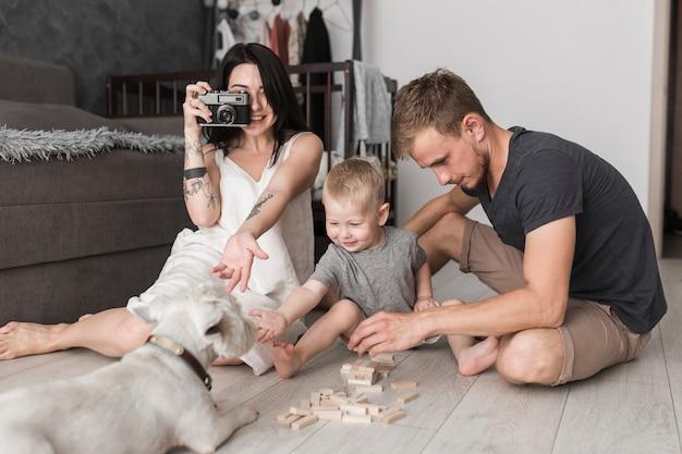 Junge frau, die foto des hundes mit der kamera sitzt nahe seinem sohn und ehemann zusammen spielend macht