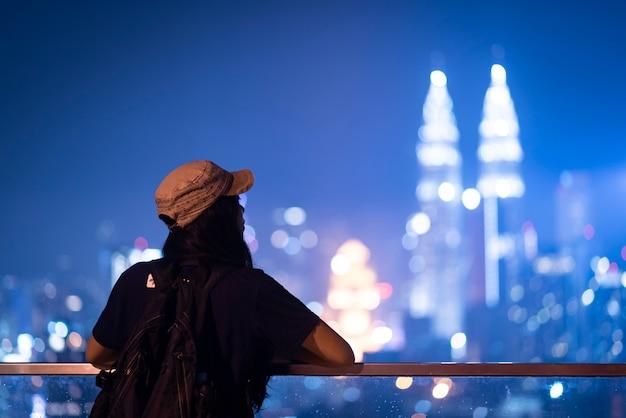Junge frau, die foto mit ihrem smartphone von petronas twins towers in kuala-lumpur am abend macht